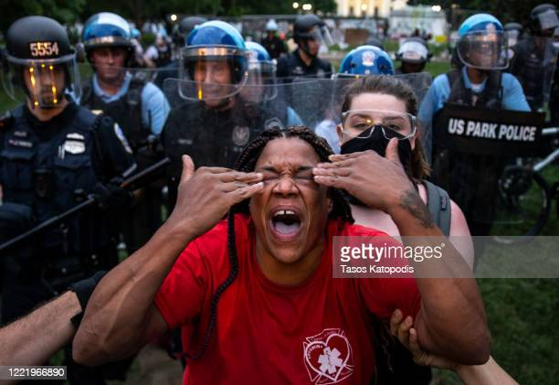 Woman reacts to being hit with pepper spray as protesters clash with U.S. Park Police after they attempted to pull down the statue of Andrew Jackson...