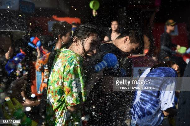 A woman reacts to being soaked in water during Songkran or the Thai New Year celebrations on Khaosan Road in Bangkok on April 14 2017 / AFP PHOTO /...