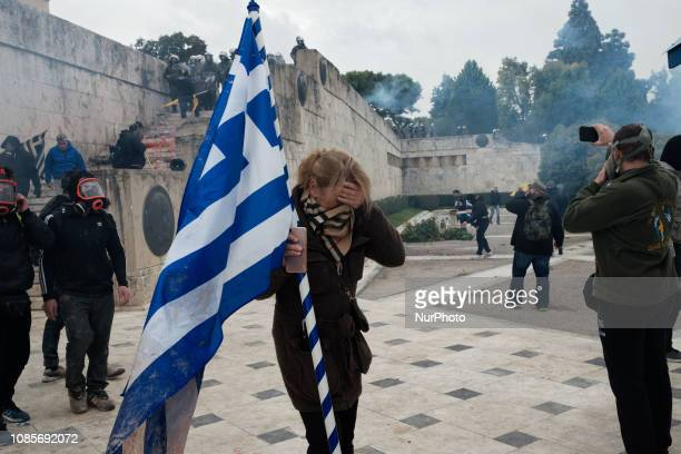 A woman reacts to tear gas during riots in a rally over Macedonia name row in Syntagma square central Athens on January 20 2019 Violent clashes broke...
