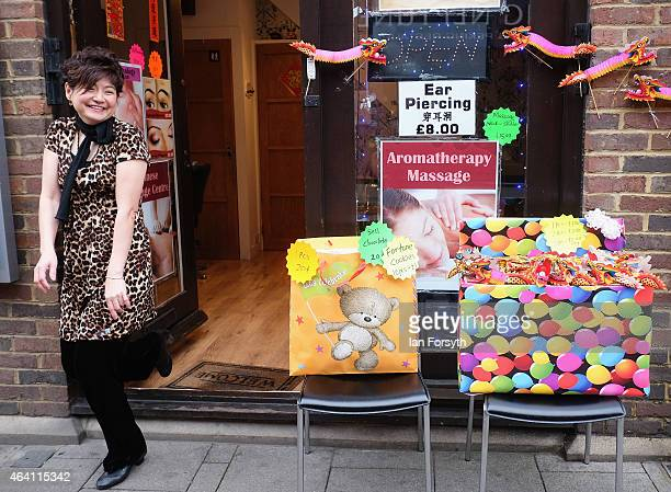 A woman reacts to the camera outside her shop as the Chinese community come together to welcome in the Chinese New Year on February 22 2015 in...