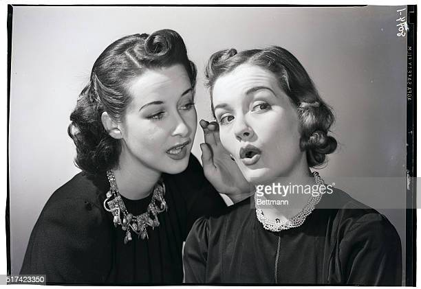 A woman reacts with interest and surprise as another woman whispers in her ear Undated photograph