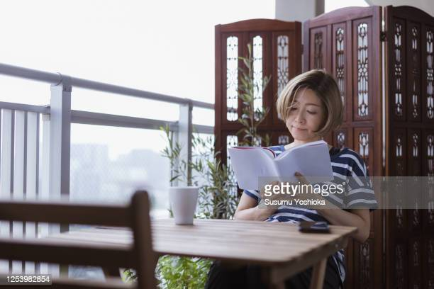 woman read analog book on the terrace room oft her house - 女性 ストックフォトと画像