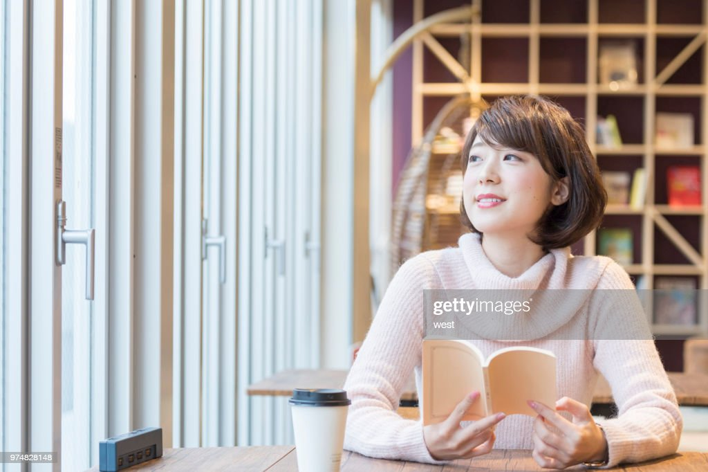 A woman reading a book at a cafe : Stock Photo