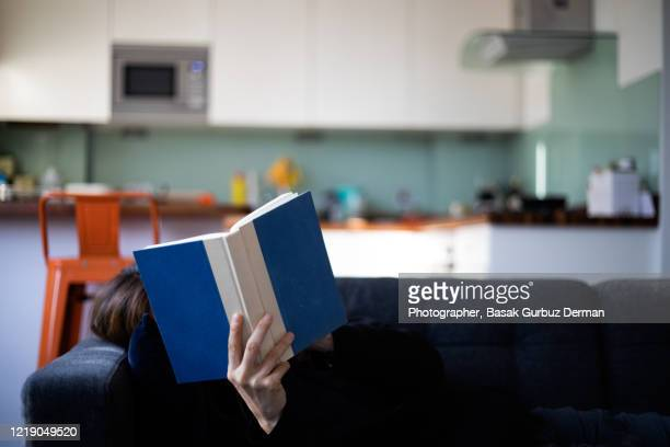 a woman reading a book at home - reading stock pictures, royalty-free photos & images
