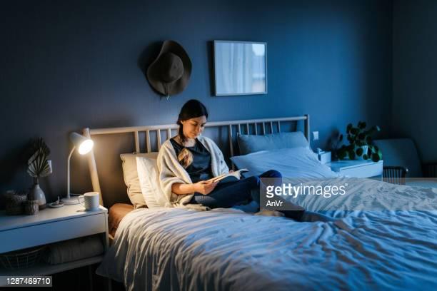 donna che legge un libro di notte - leggere foto e immagini stock