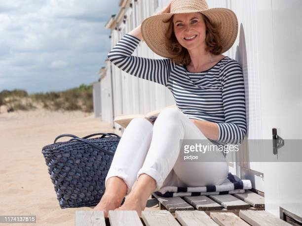 woman reading a book at the beach. - coastline stock pictures, royalty-free photos & images