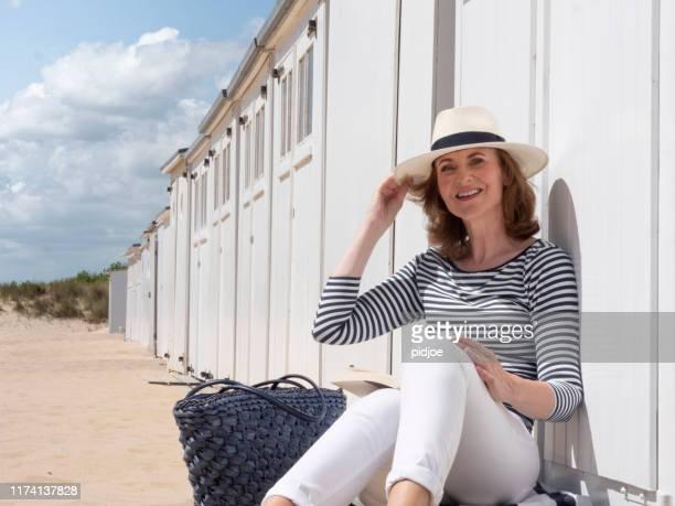 vrouw het lezen van een boek op het strand. - strohoed stockfoto's en -beelden