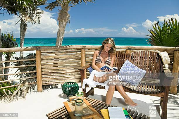 Woman reading a book by beach