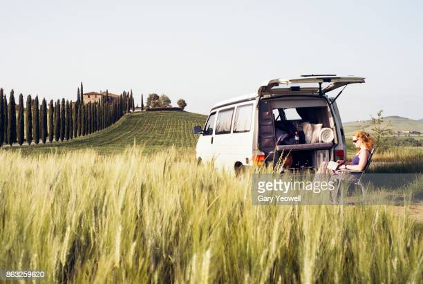 Woman reading a book by campervan in Tuscany landscape