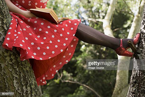 Woman reading a book in a tree