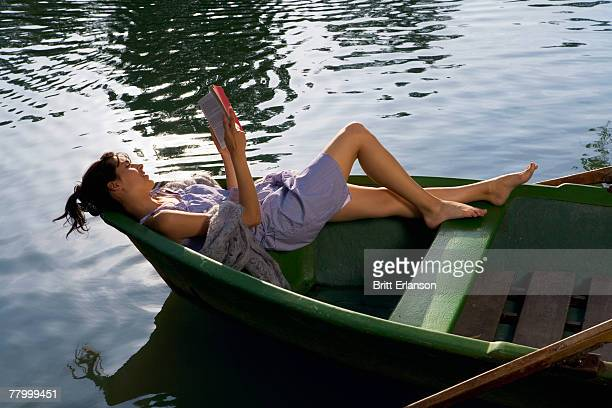 Woman reading a book in boat