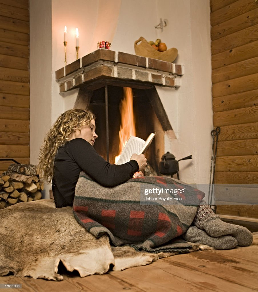 a woman reading a book in front of a fireplace sweden ストックフォト