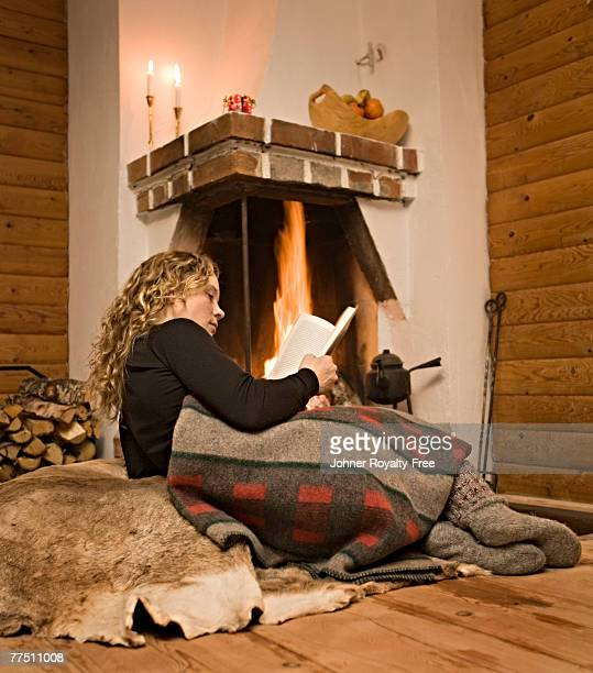 A woman reading a book in front of a fireplace Sweden.