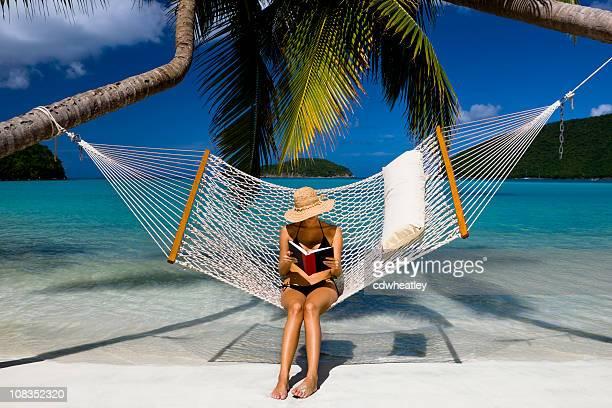 Femme lisant un livre dans un hamac sur la plage dans les Caraïbes