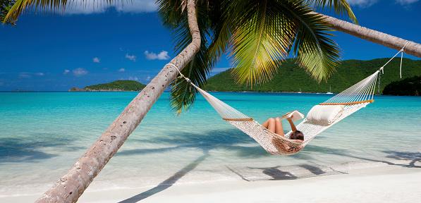 woman reading a book in hammock at the Caribbean beach 181079364