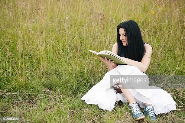 Frau liest ein Buch auf dem Meadow