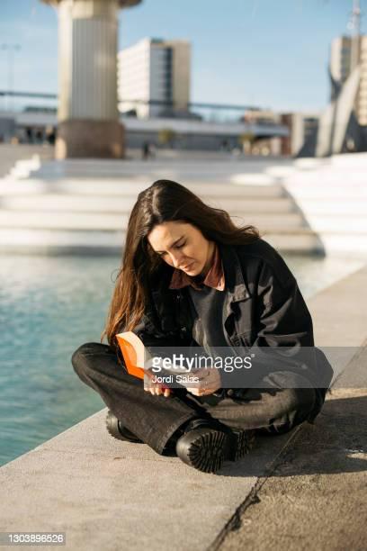 woman reading a book next to a lake - editorial - fotografias e filmes do acervo