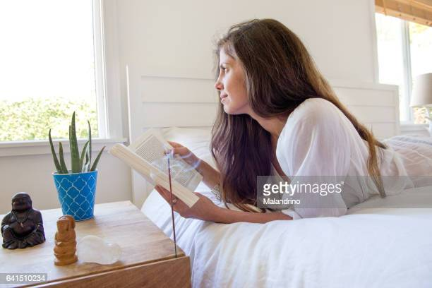Woman reading a book on a bed