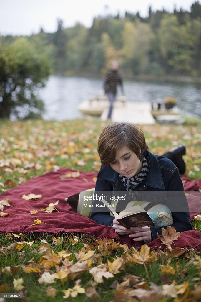 A woman reading a book on a blanket. : Stock Photo