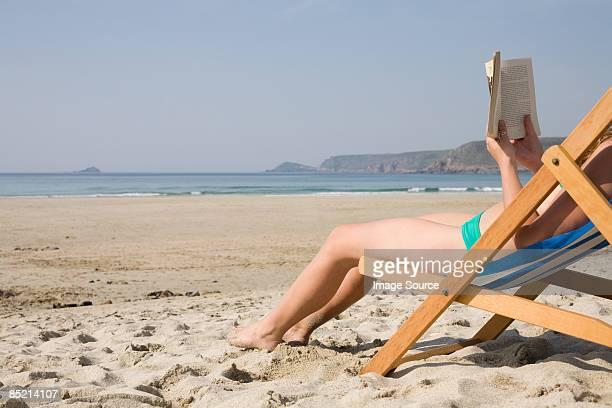 Woman reading a book on an empty beach