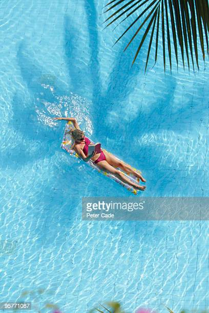 woman reading a book on lilo in pool