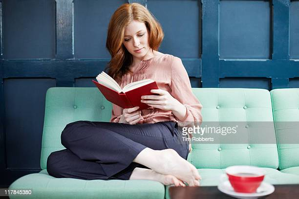 woman reading a book on sofa. - reading book stock pictures, royalty-free photos & images