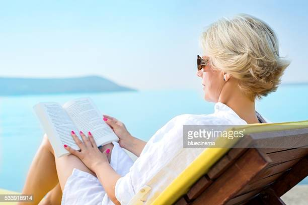 woman reading a book on the beach - mid adult women stock pictures, royalty-free photos & images