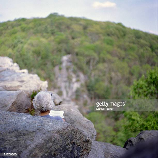 Woman reading a book overlooking a cliff in the summer. A nice comfortable reading location on rocks in the American Northeast.