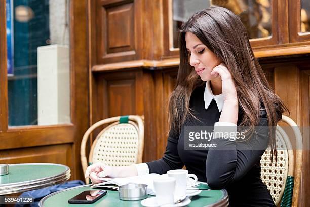 Femme lisant un livre tout en sirotant un café dans une cafétéria