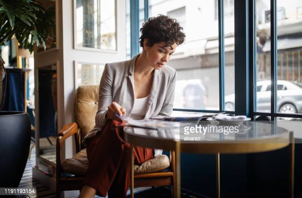 woman reading a magazine at cafe - magazine stock pictures, royalty-free photos & images