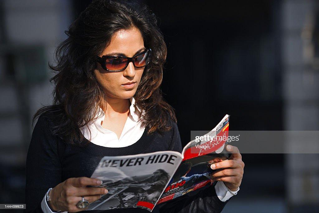 Woman reading a magazine : Stock Photo