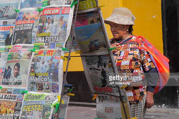 Woman reading a newspaper at a newsstand in Avenida Miguel Grau.
