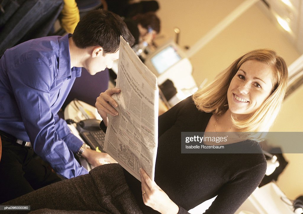 Woman reading a newspaper in office, portrait : Stockfoto