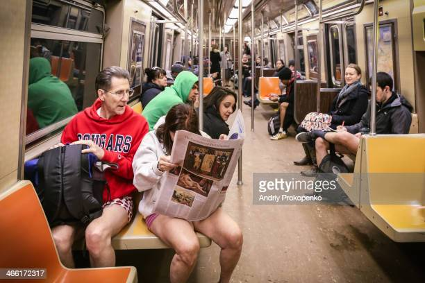"""Woman reading a newspaper on the train during the """"No Pants Subway Ride"""" on January 12, New York City, USA"""