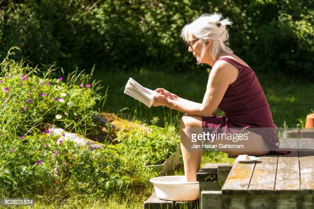 woman reading and having a footbath on cottage porch - old lady feet stock pictures, royalty-free photos & images