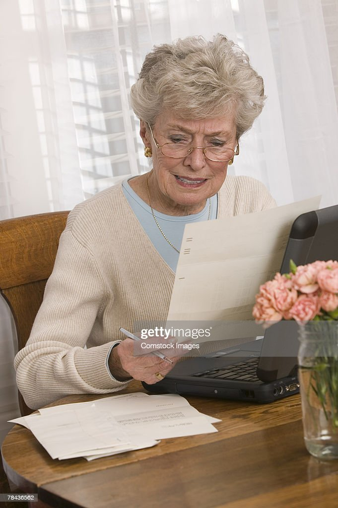 Woman reading and using laptop : Foto de stock