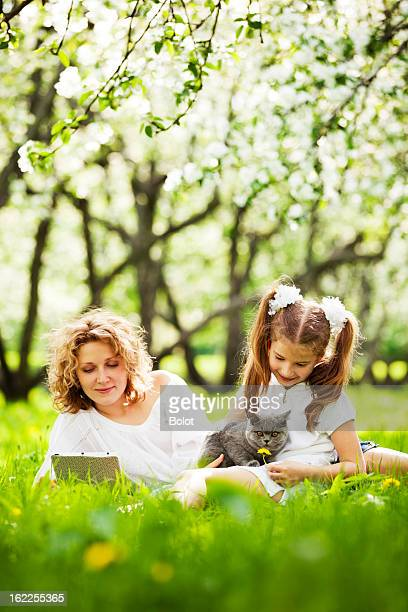 Woman reading and young girl with cat outdoors in the grass
