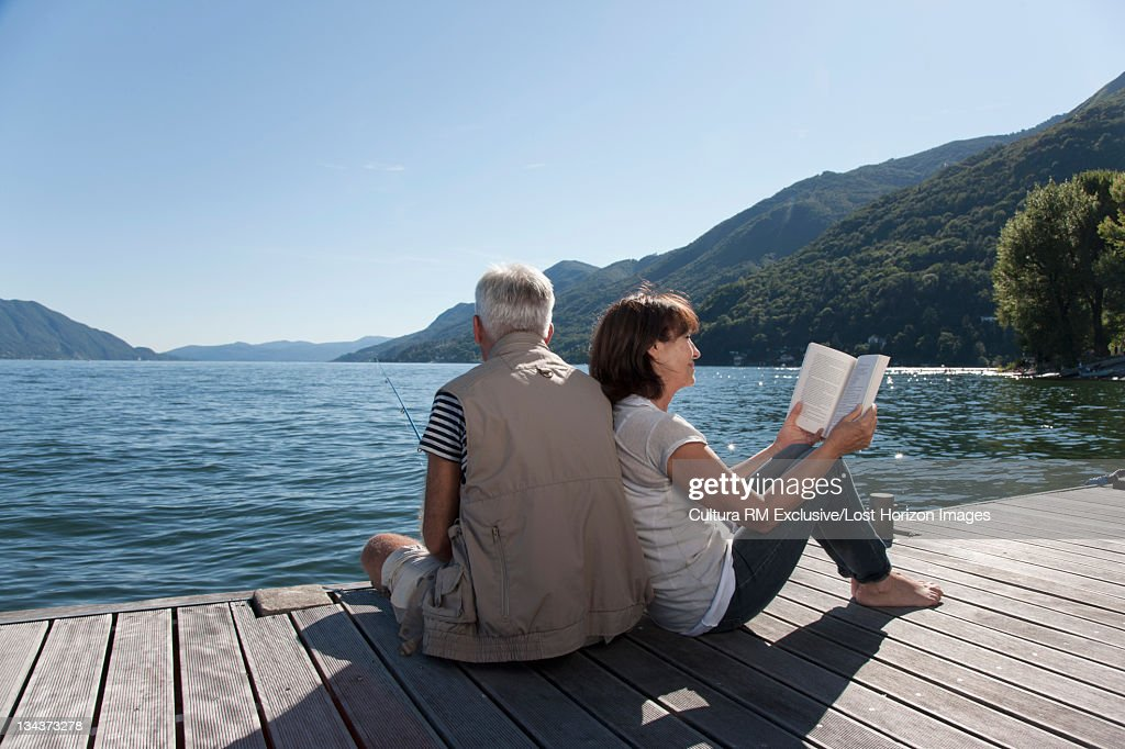 Woman reading as husband fishes : Stock Photo