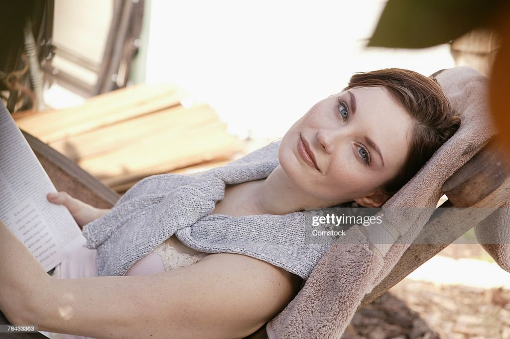 Woman reading as she reclines in chair outdoors : Stockfoto