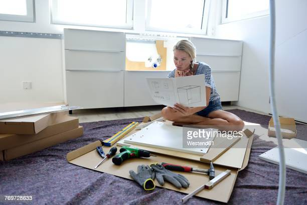 Woman reading assembly instructions at home