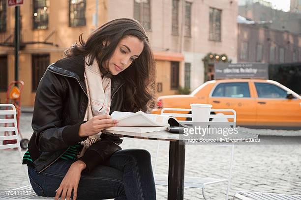 Woman reading at sidewalk cafe