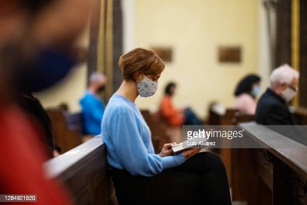 woman reading bible and praying in church - christianity stock pictures, royalty-free photos & images