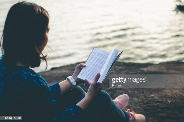 woman reading book against lake - literatur stock-fotos und bilder