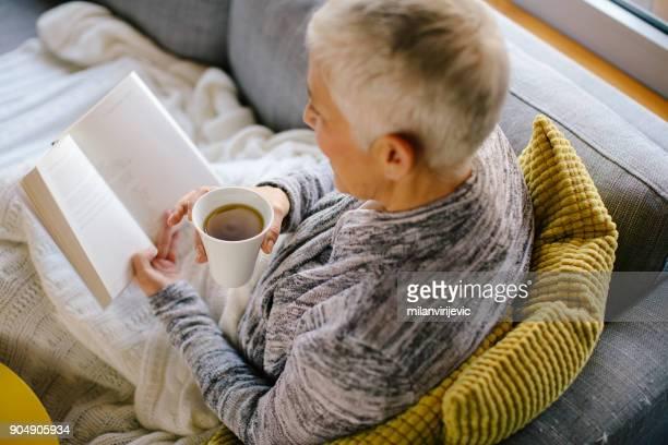 Frau liest ein Buch und Trinken Kaffee