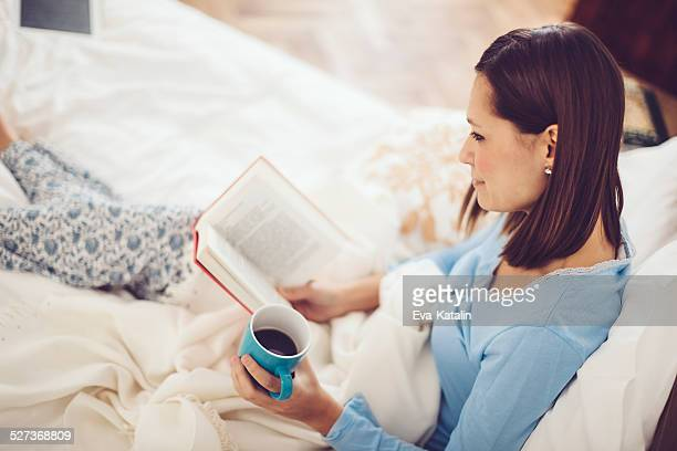 Woman reading book and drinking morning coffee in the bed