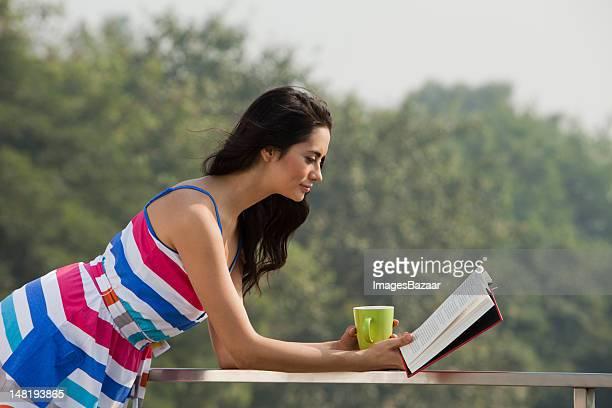 Frau liest ein Buch und trinken Tee auf Balkon