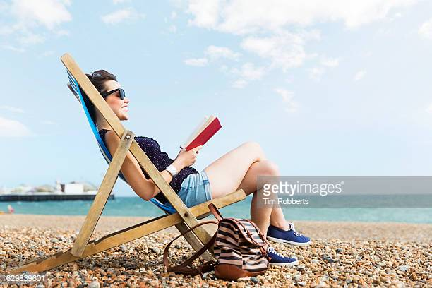 woman reading book at beach - sussex stock pictures, royalty-free photos & images
