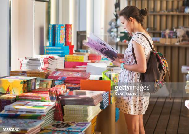 woman reading book at store - book store stock photos and pictures