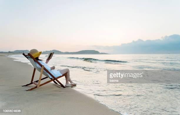 vrouw leesboek op het strand - waterkant stockfoto's en -beelden