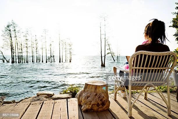 Femme lisant livre sur le lac